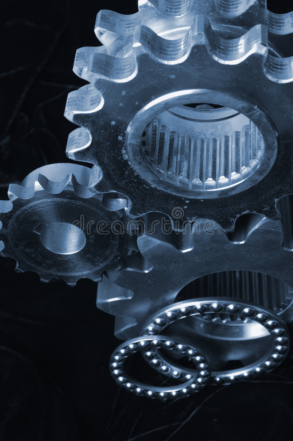 Gear menagerie. Three gears and fine ball-bearings shot against black velvet royalty free stock photo