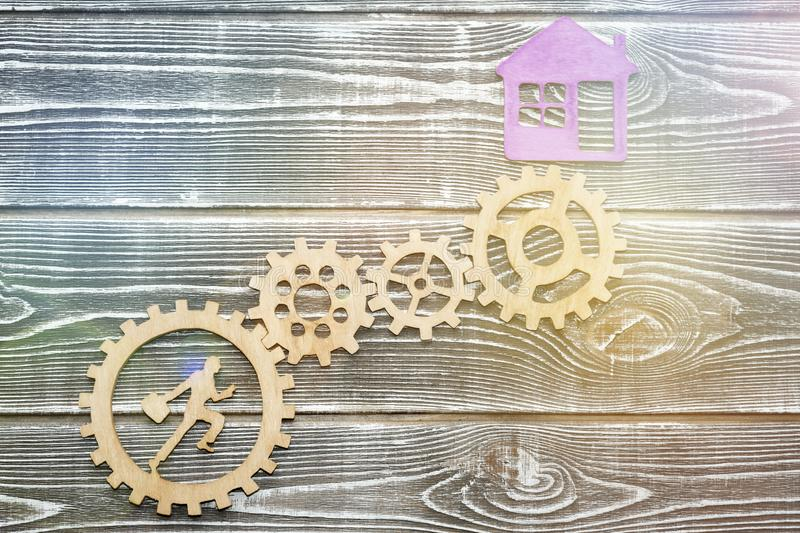 Gear, running worker, house on a wooden background. stock image