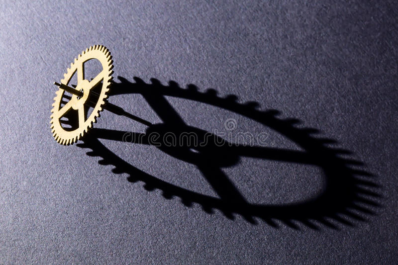 Gear shadow. Geometry long gear shadow on the black background royalty free stock image