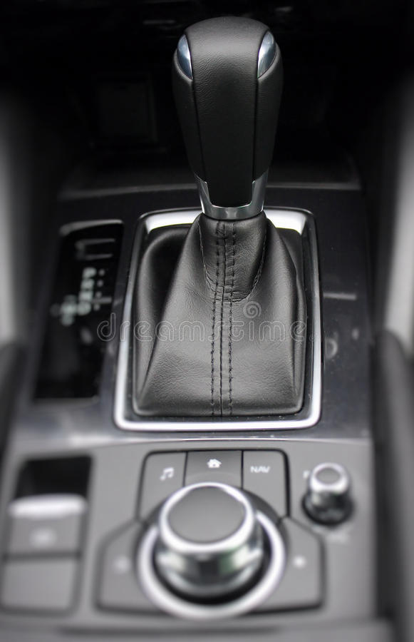Gear shift knob in leather car interior detailed. Gear shift knob in leather car interior closeup royalty free stock photos