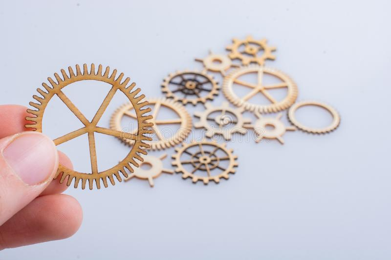 Gear wheel in hand on white background as concept of engineering royalty free stock images