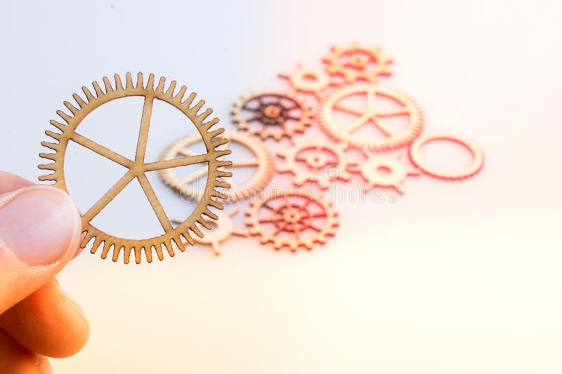Gear wheel in hand on white background as concept of engineering stock photo