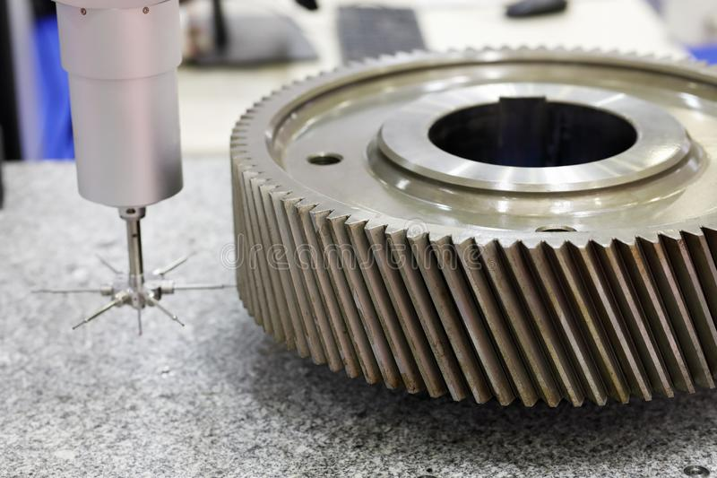 Gear wheel measuring using CMM. Gear wheel measuring using coordinate measuring machine with touch trigger probe. Selective focus royalty free stock photo