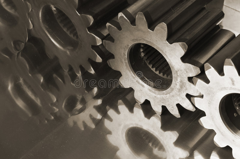 Gear-wheel menagerie. Gears,cogs in brownish connecting against titanium stock photo
