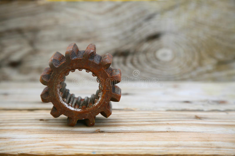 Gear on wooden background, Machine parts or spare parts, industry background, old gear or damaged gear from hard work.  royalty free stock image