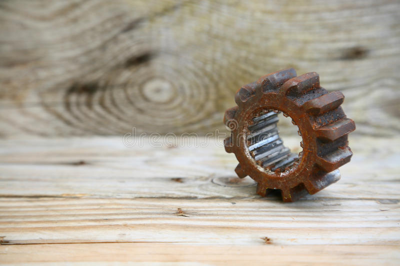 Gear on wooden background, Machine parts or spare parts, industry background, old gear or damaged gear from hard work.  stock photo