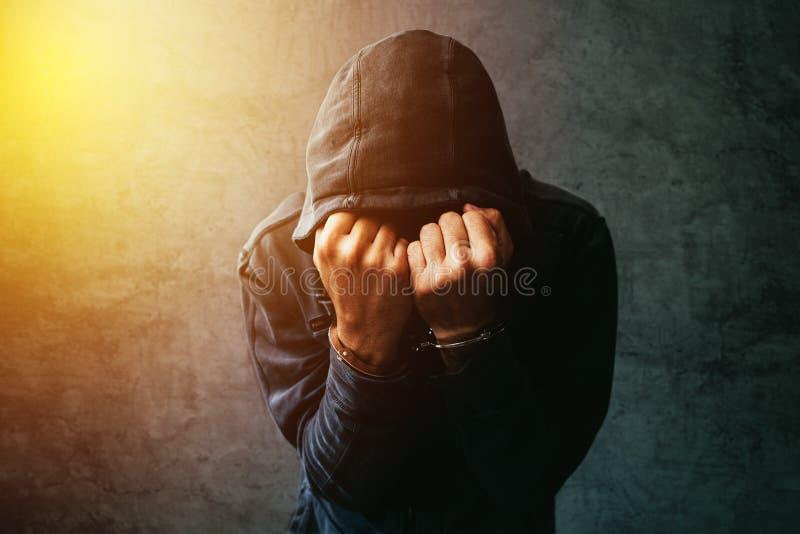 Gearresteerde computerhakker met handcuffs die jasje met een kap dragen royalty-vrije stock fotografie
