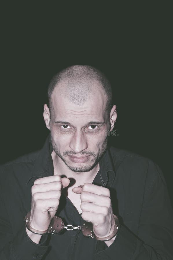 Gearresteerde misdadiger Gearresteerde misdadiger met handcuffs op zijn handen stock foto