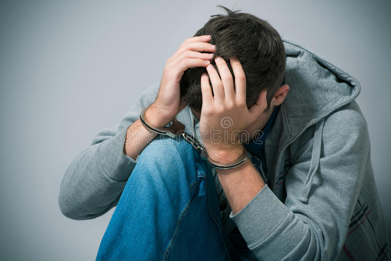 Gearresteerde tiener met handcuffs stock foto
