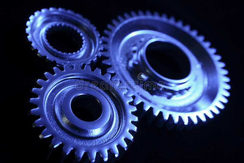 Gears. Three steel gears connecting together blue tone royalty free stock photos