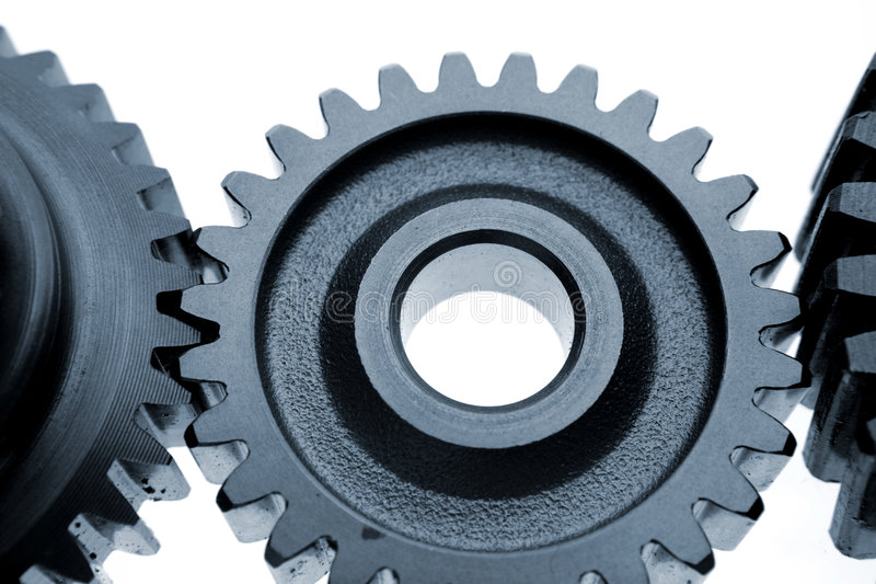 Gears. Three metal gears connecting on white stock photos
