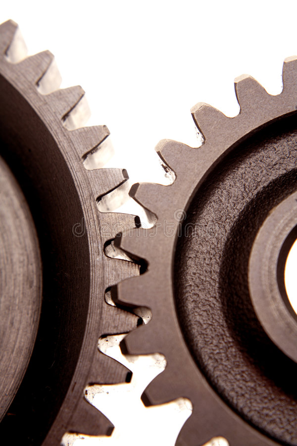 Gears. Two gears meshing together on white royalty free stock photography