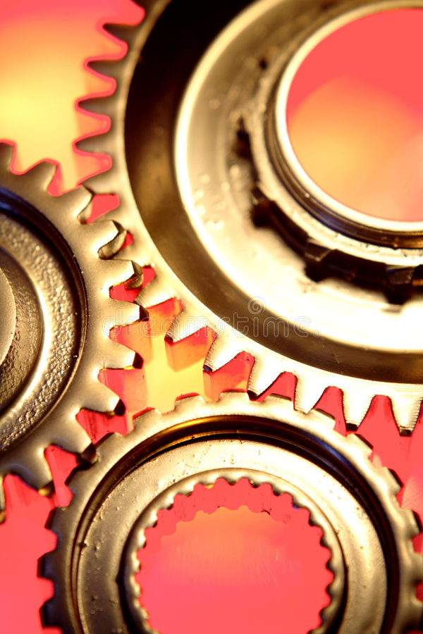 Gears. A background of gold gears or cogs on red royalty free stock photo