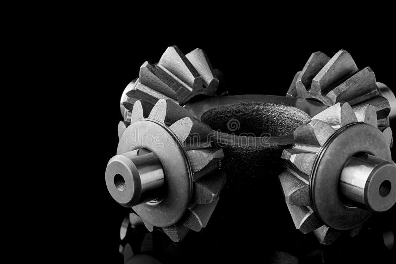 Gears, bearings and differential stars lie on the table close-up. Gears, bearings and differential are on the table in the dark. Can be used as a background stock image