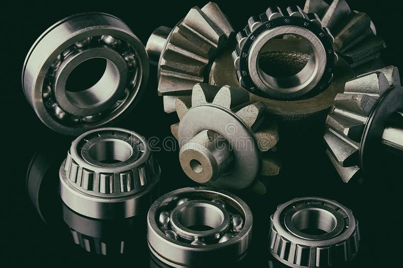 Gears, bearings and differential stars lie on the table close-up. Gears, bearings and differential are on the table in the dark. Can be used as a background royalty free stock images
