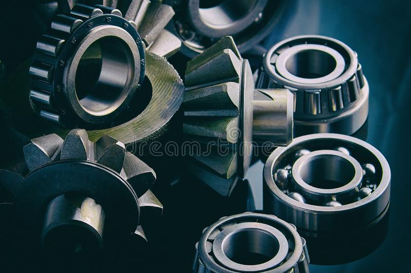 Gears, bearings and differential stars lie on the table close-up. Gears, bearings and differential are on the table in the dark. Can be used as a background stock images