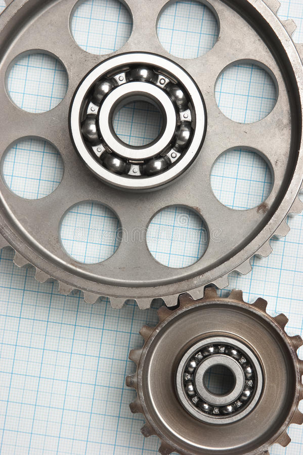 Gears and bearings. On graph paper stock photos