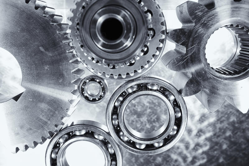 Gears, cogs and ball-bearings. Titanium and steel gears and ball-bearings, industrial engineering parts in metal blue toning stock images
