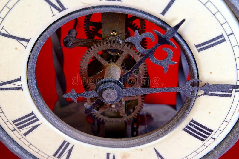 Old metal dusty mechanical clock with moving gears and screws. Brass cog wheels, Close view of old rusty clock mechanism. With gears and cogs. Element of design royalty free stock images