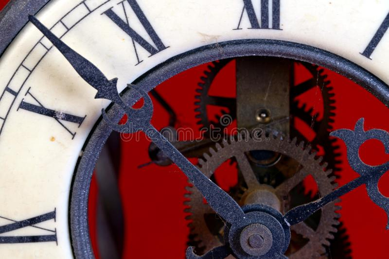 Old metal dusty mechanical clock with moving gears and screws. Brass cog wheels, Close view of old rusty clock mechanism. With gears and cogs. Element of design stock images