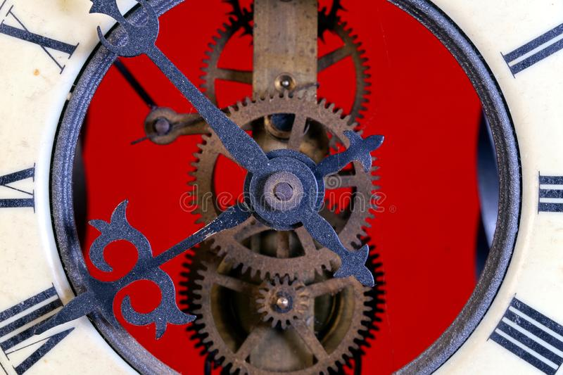 Old metal dusty mechanical clock with moving gears and screws. Brass cog wheels, Close view of old rusty clock mechanism. With gears and cogs. Element of design stock photo