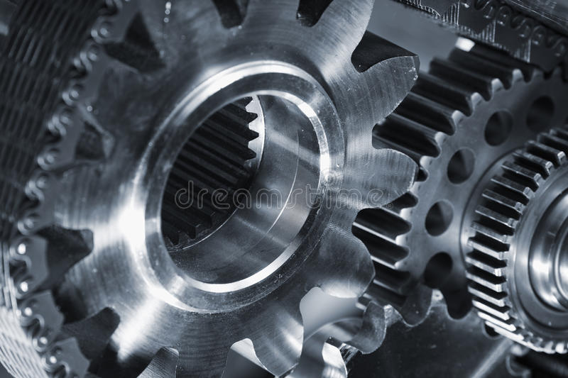 Gears, cogs, titanium and oil, lubricants. Smaller gears from aerospace industry with oil and lubricants. blue toning concept royalty free stock photography