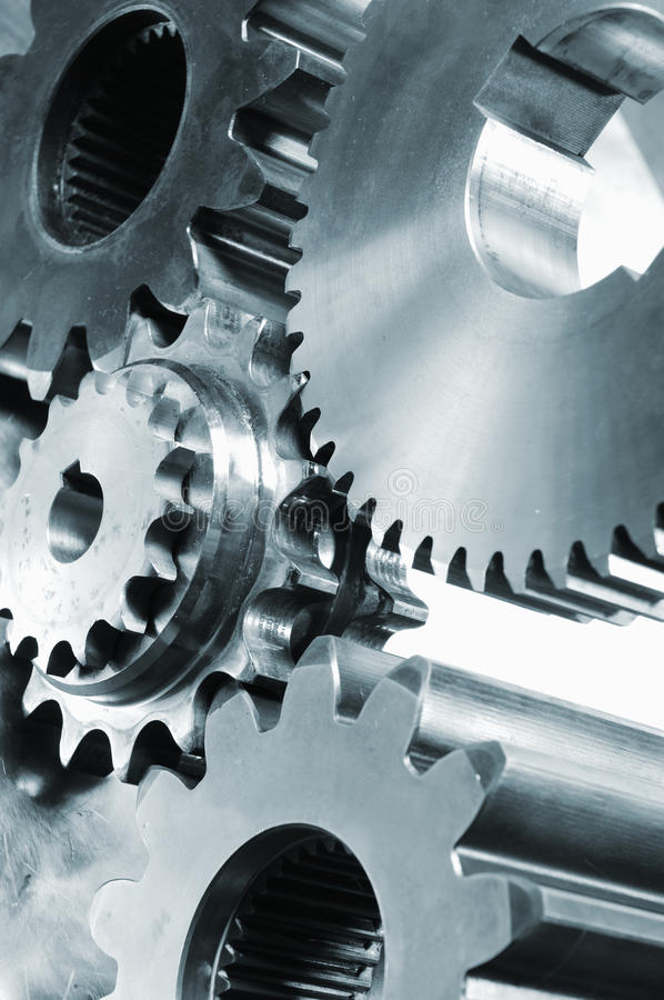 Gears, cogs, titanium and steel. Giant and small gears and cogs in a blue metal toning concept royalty free stock image