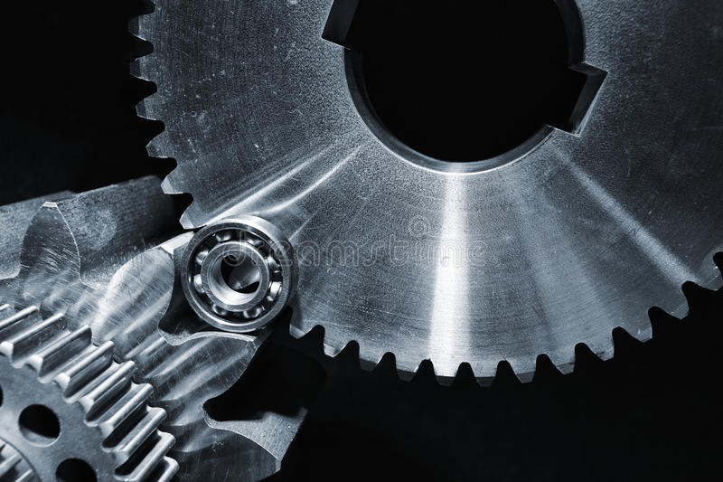 Gears and cogwheels set against black background. Aerospace gears and cogs set against a black velvet background royalty free stock photos