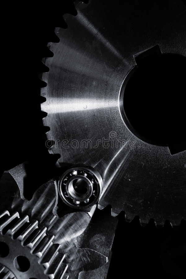 Gears and cogwheels set against black background. Aerospace gears and cogs set against a black velvet background royalty free stock photography