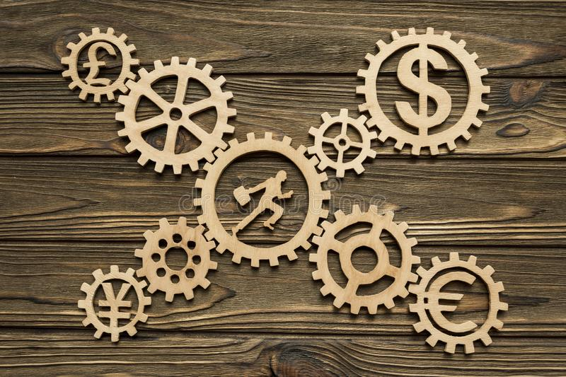 Gears. currency, office worker. On a wooden background. business. finance stock image