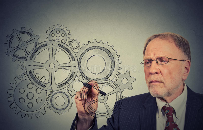 Gears and ideas. Engineer or elderly businessman leader. stock photography