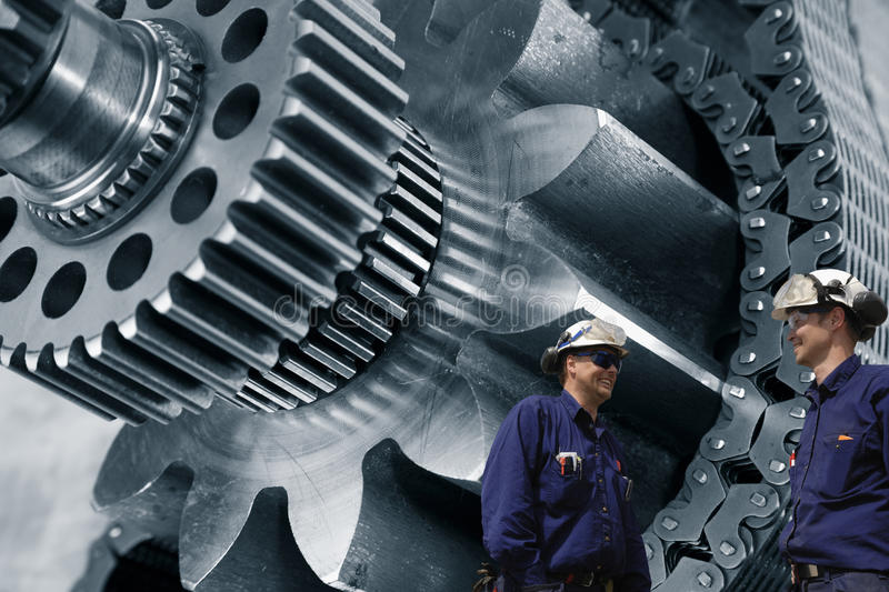 Gears machinery and engineering. Engineers, mechanics working with giant gears machinery, driven by a timing chain stock photo