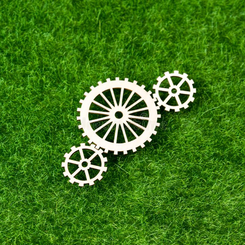 Gears made of wood on the background of artificial green grass. royalty free stock images
