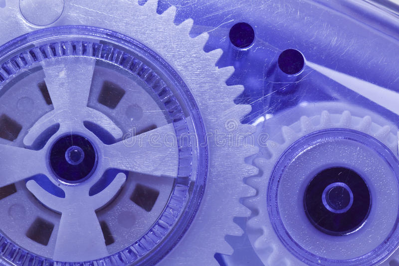 Gears of a mechanical device. Gears in purple plastic. Machinery. Macro royalty free stock photo