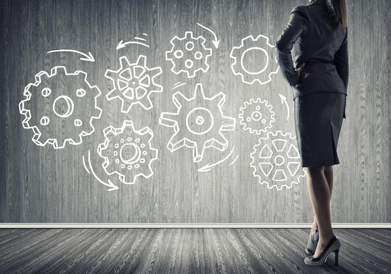 Gears mechanism as teamwork concept. Bottom view of businesswoman and teamwork drawn concept on wall royalty free stock photography