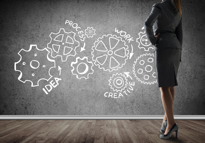 Gears mechanism as teamwork concept. Bottom view of businesswoman and teamwork drawn concept on wall royalty free stock images