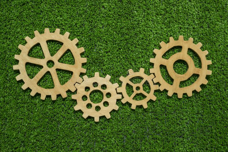 Gears of natural wood on a background of green grass symbolize green technology. Concept of ideas, cooperation, strategy, teamwork. business royalty free stock photo