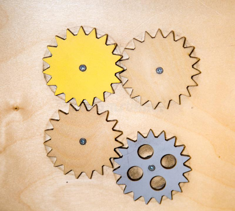 Gears wooden yellow brown gray connected with each other. Toys stock photography