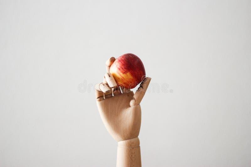 Gearticuleerde houten hand die een rode appel op witte achtergrond houden royalty-vrije stock afbeeldingen