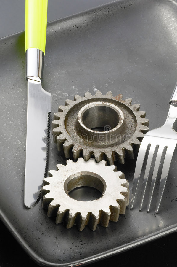Gearwheels on a plate. Gearwheels on a black plate with knife and fork royalty free stock image