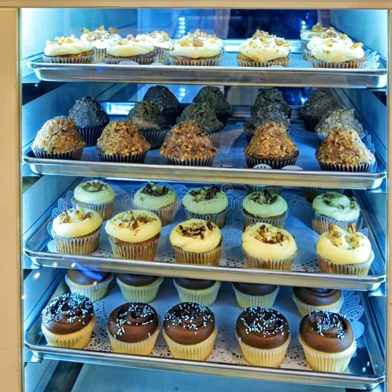 Geassorteerd cupcakes en desserts op de bakkerij storefront stock fotografie