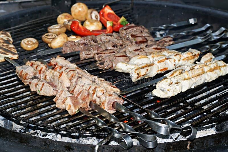 Geassorteerd heerlijk geroosterd vlees met groente over de steenkolen op een barbecue stock foto's