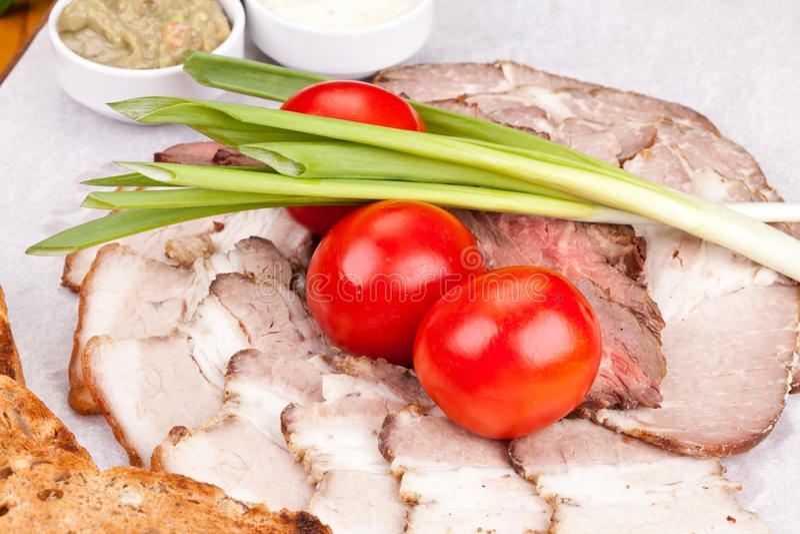 Geassorteerd koud vlees met geroosterd brood, kersentomaten, ui en sausen op witte plaat royalty-vrije stock foto
