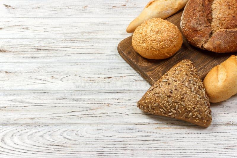 Geassorteerd van brood op witte houten achtergrond Hoogste mening met exemplaarruimte stock afbeeldingen