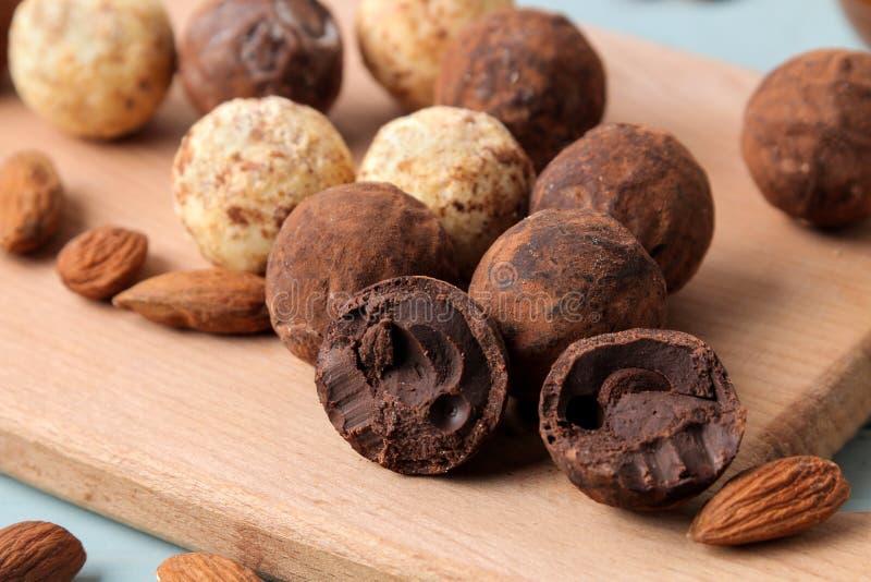 Geassorteerde chocolade Suikergoedballen van verschillende types van chocolade op een houten raad op een blauwe houten lijst aman stock fotografie