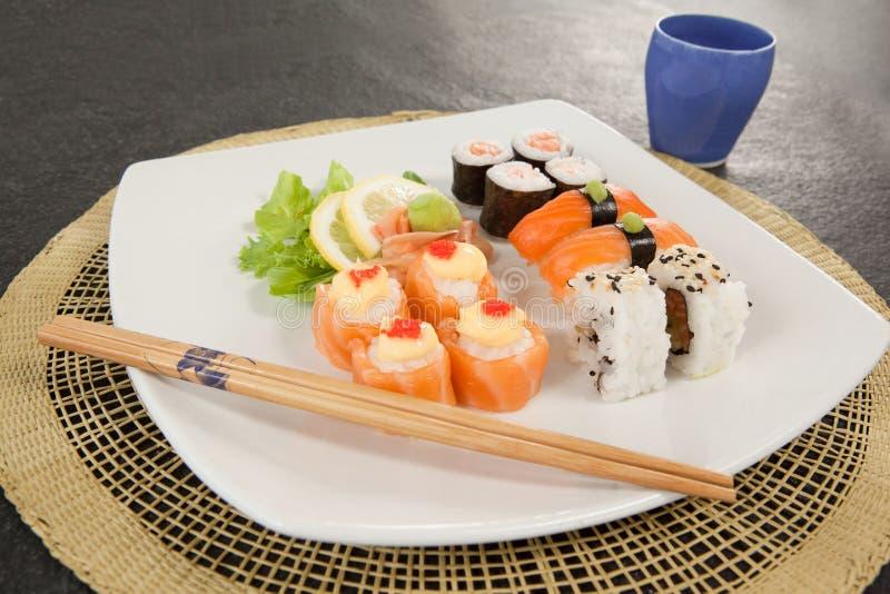 Geassorteerde die sushireeks met eetstokjes en glas op sushimat wordt gediend stock afbeelding