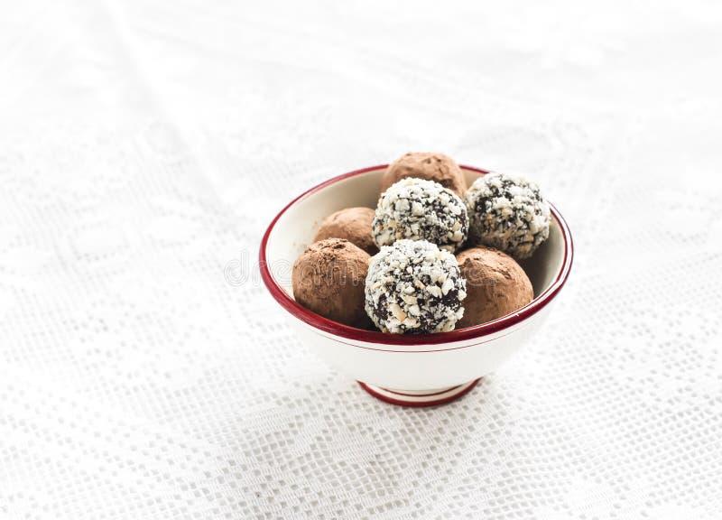 Geassorteerde eigengemaakte donkere chocoladetruffels in een witte ceramische kom stock fotografie