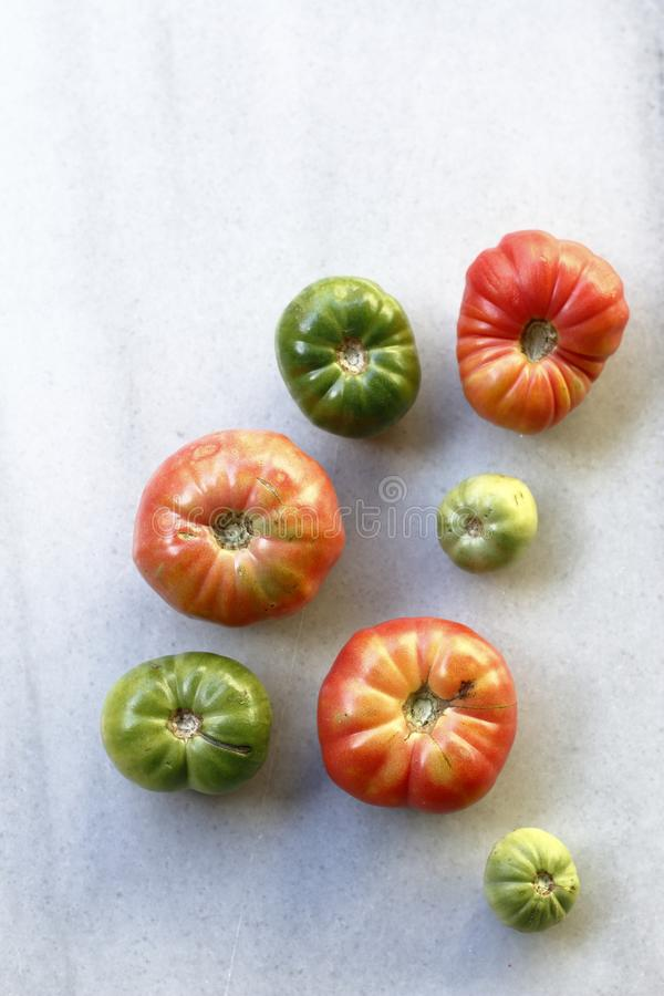 Geassorteerde en heerlijke die tomaten op marmer worden verspreid stock fotografie