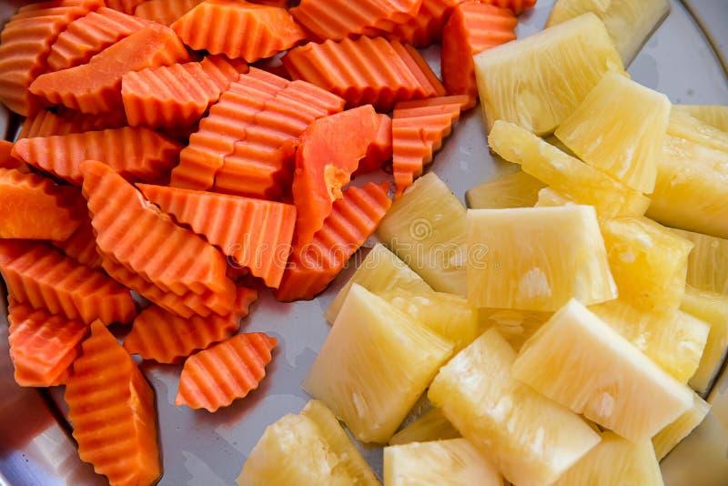 Geassorteerde exotische verse vruchten dia en stuk van vers fruit op witte plaat ananas, papaja Ontbijt in self - service met p stock fotografie