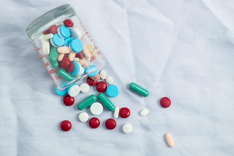 Geassorteerde farmaceutische geneeskundepillen, tabletten en capsules en fles gress stock foto